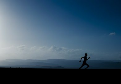 człowiek biegnący, w tle góry i niebo, chmury w tyle