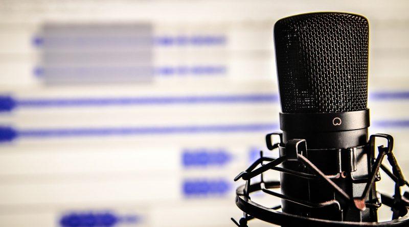 mikrofon do podcastu, w tle monitor pokazujący, że dźwięk z mikrofonu jest nagrywany