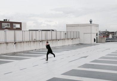 chłopak biegnący sprintem przez parking