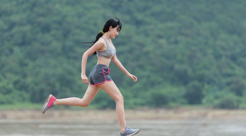 kobieta biegnąca nad brzegiem jeziora, w oddali drzewa