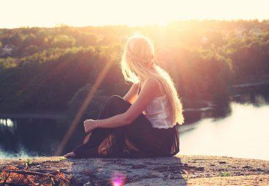 kobieta siedząca na ziemi, w tle słońce i las