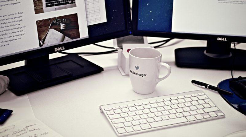 Komputer z wynajmu komputerów składający sie z dwóch monitorów i klawiatury leżących na stole razem z kubkiem